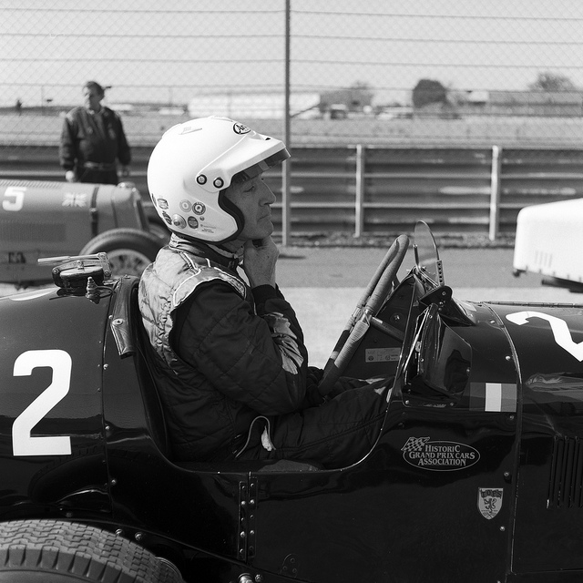 A driver straps up his helmet in aa black ERA, photographed in black and white on a Mamiya C330F.