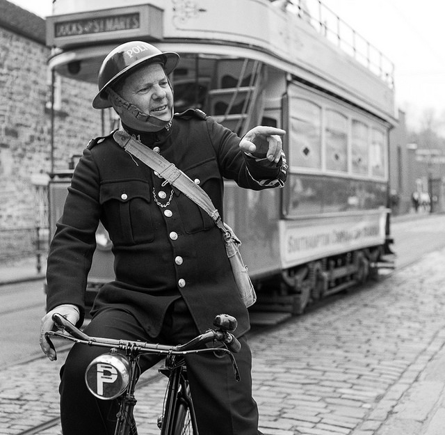 A re-enactor dressed as a police man on a bike at Crich Tramway