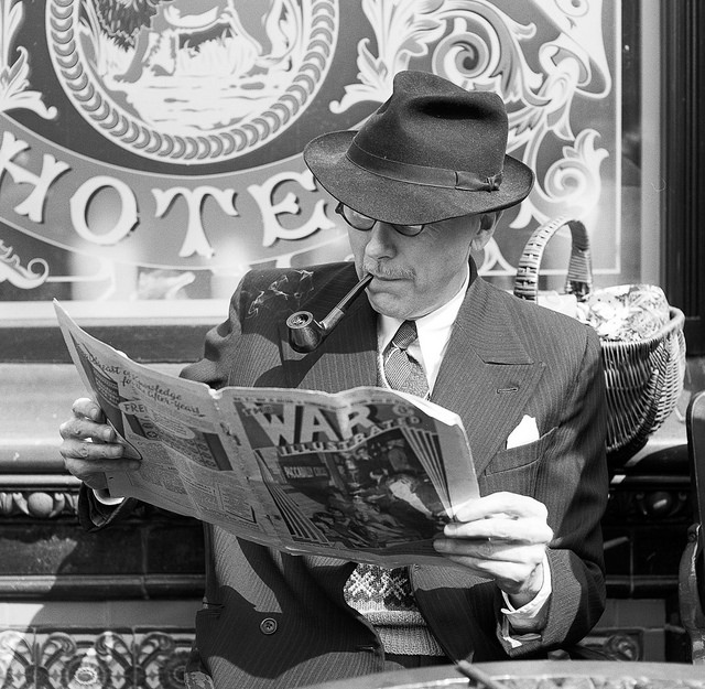 A man smartly dressed in 1940s clother reads a paper outside the pub at Crich tramway.