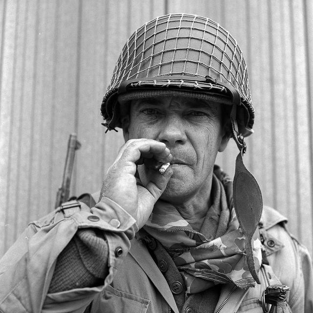 A re-enactor dressed in WW2 American soldier uniform smoking a cigarette.