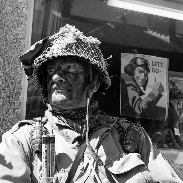 A soldier at the Haworth 1940s weekend in front of a Let's Go propaganda poster