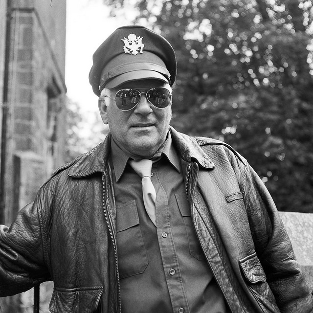 An American Air Force gent wearing aviators in which I am reflected taking a photograph.