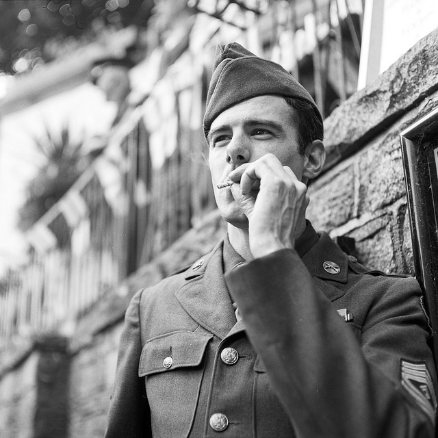 A man dressed as a WW2 airman smoking a cigarette
