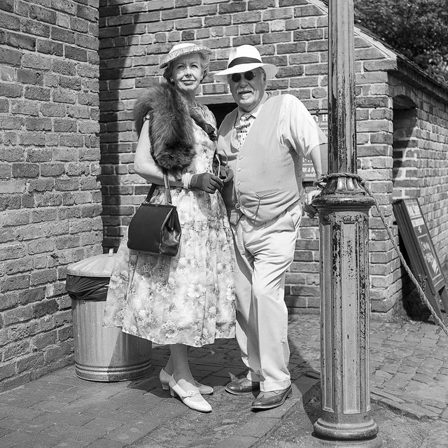 A couple dressed in 1940s attire stand by a lamp post at the Black Country Museum.