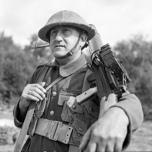 A soldier carries a Lewis gun over his shoulder. I liked the way the arm down to the gun, then into the soldiers face. This person could have been anyone's relative sent to the front to fight.
